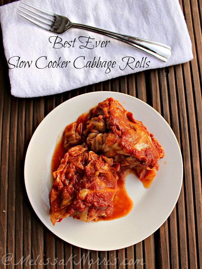 "Two cabbage rolls sitting on a white plate with a fork and napkin off to the side. Text overlay says, ""Best Ever Slow Cooker Cabbage Rolls""."