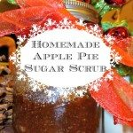 """Picture of a Mason Jar filled with apple pie scented sugar scrub. Jar is decorated with red ribbon, and red Jingle bells with sparkled garland is in the background. Text overlay says, """"Homemade Apple Pie Sugar Scrub""""."""