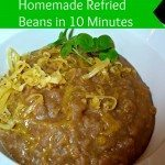 """Close up image of refried beans served in a white bowl, and garnished with cheddar cheese and cilantro. Text overlay says """"Homemade Refried Beans in 10 Minutes""""."""