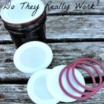 """Image of a jar of jelly sitting on a white washed table with reusable Tattler lids and rings scattered in front. Text overlay says, """"Reusable Canning Tattler Lids...Do They Really Work?"""""""