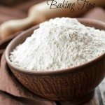 """Pinterest Pin image containing a blow of fresh ground flour and a rolling pin in the background. Text overlay says """"Grinding Your Own Flour plus 6 Fresh Flour Baking Tips""""."""