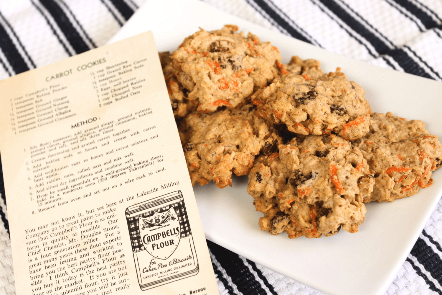 Plate of healthy carrot cookies on table with old newspaper bulletin