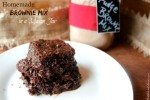 """Picture of a white plate holding a a fudgy brownie. Sitting on the table in the background is a Mason jar filled with homemade brownie mix. Text overlay says """"Homemade Brownie Mix in a Mason Jar""""."""