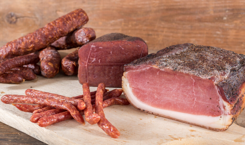 smoked sausages and meat on wooden table