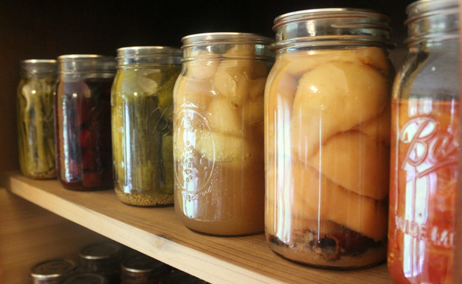 Jars of home canned food lining a pantry shelf.