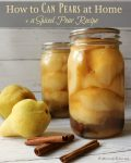 "Two jars of canned pears with two pears and three cinnamon sticks sitting on a wooden surface. Text overlay says, ""How to Can Pears at Home + a Spiced Pear Recipe""."
