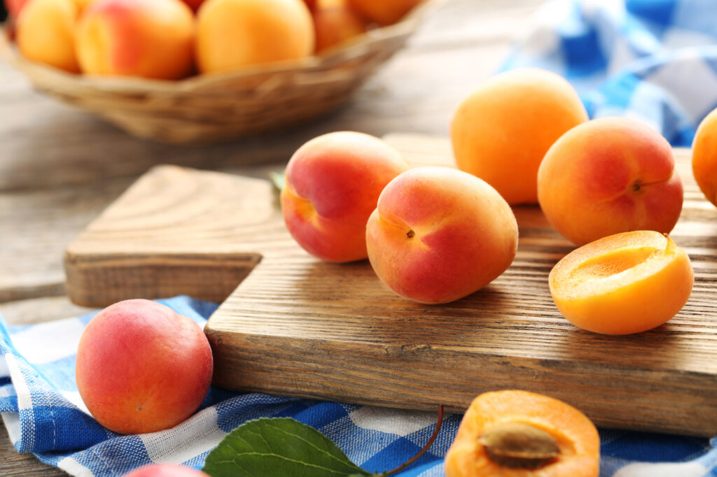 Apricots on a cutting board on a table.