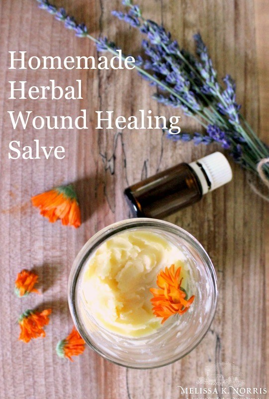 "Image of a jar of salve and some dried flowers with a bottle of essential oil. Text overlay says, ""Homemade Herbal Wound Healing Salve""."