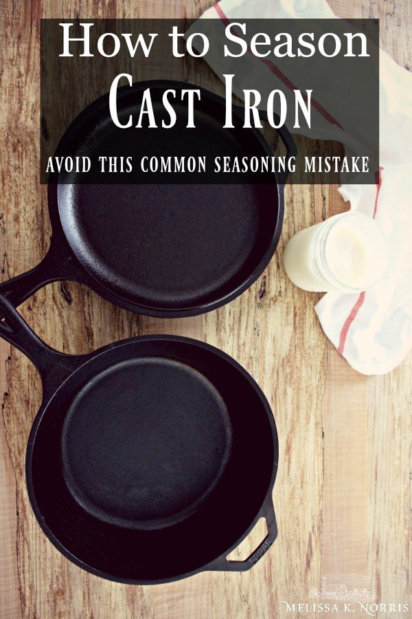 """Two cast iron pans sitting on a wood table with a cloth and jar of lard. Text overlay says, """"How to Season Cast Iron: Avoid this Common Seasoning Mistake""""."""