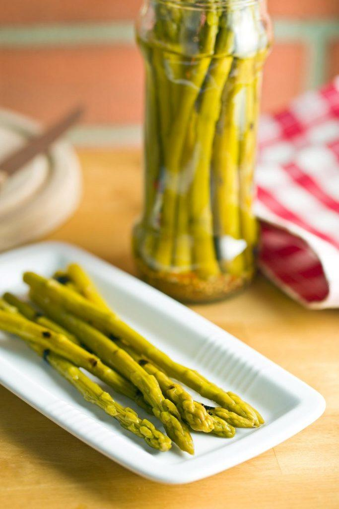 Pickled asparagus piled on a white plate with a jar of pickled asparagus in the background.