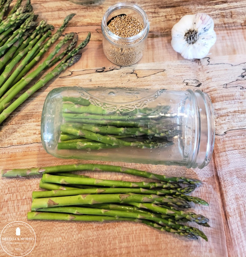 asparagus going into Mason jar clove of garlic and mustard seed on table