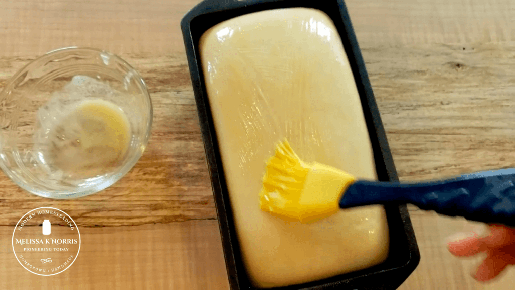 brushing melted butter on top of sourdough sandwich bread