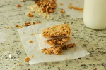 Homemade granola bars stacked up with parchment paper in between layers and granola on the counter behind them.