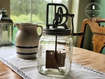 antique butter churn on table
