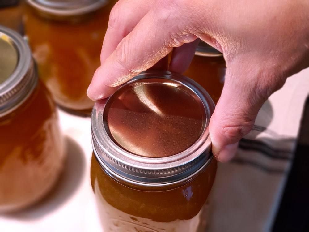 A hand screwing on a mason jar lid.