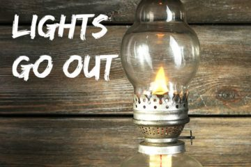 "Picture of an antique kerosene lamp sitting on a bed of hay with barn wood in the background. Text overlay says, ""4 Things You Need When the Lights Go Out""."