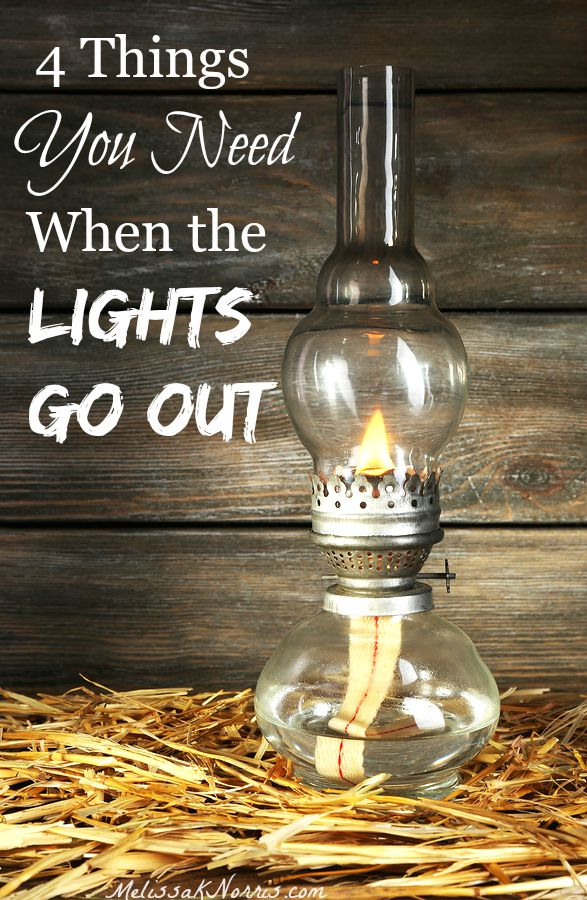 """Picture of an antique kerosene lamp sitting on a bed of hay with barn wood in the background. Text overlay says, """"4 Things You Need When the Lights Go Out""""."""