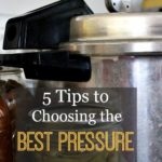 A pressure canner with two jars of pressure canned food next to it.