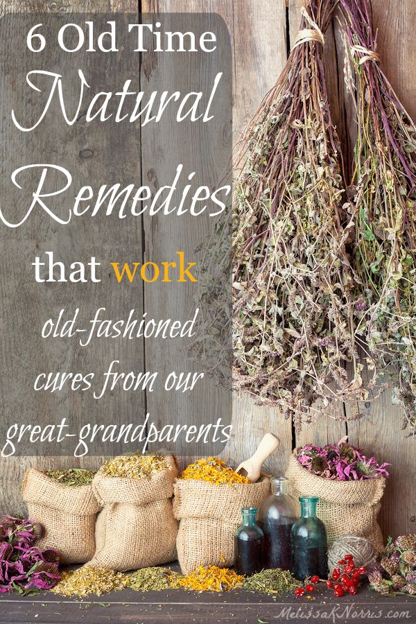 "Image of a workbench and wood wall with dried herbs hanging and bags of dried flowers and herbs. Text overlay says, ""6 Old Time Natural Remedies that Work: Old fashioned cures from our great grandparents."""