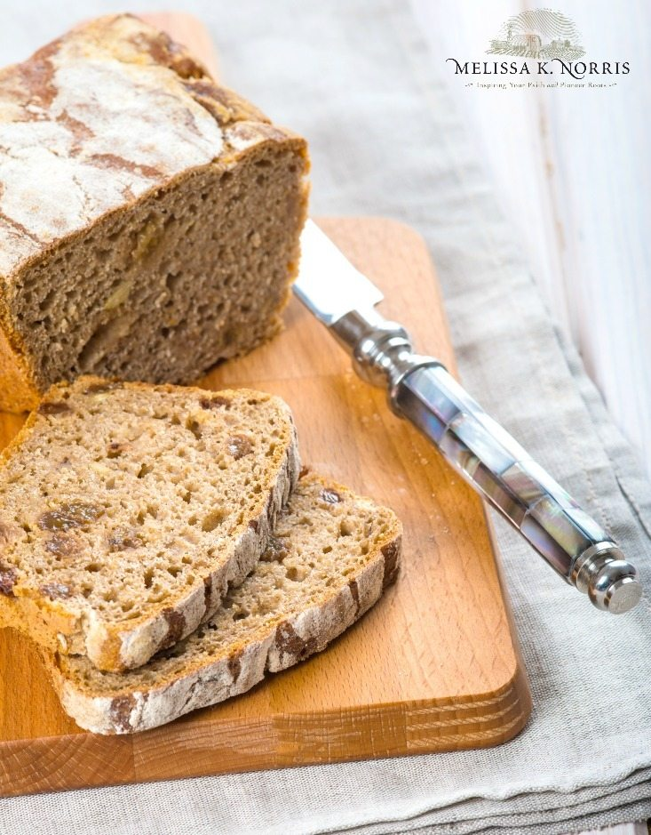 """Image of a loaf of bread being sliced on a cutting board. Text overlay says, """"Homesteading for Beginners: 9 Transition Tips from City Life to Homesteader""""."""
