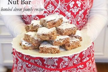 """Woman in a red and white apron holding a plate of date nut bars. Text overlay says, """"Old Fashioned Italian Date Nut Bar""""."""