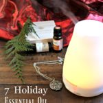 """Image of an essential oil diffuser with bottles of essential oil, an essential oil diffuser necklace, a cedar bow, and red velvet draped in the background. Text overlay says, """"7 Holiday Essential Oil Blends for a Natural Homestead """"."""
