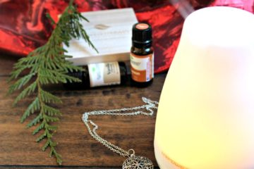 "Image of an essential oil diffuser with bottles of essential oil, an essential oil diffuser necklace, a cedar bow, and red velvet draped in the background. Text overlay says, ""7 Holiday Essential Oil Blends for a Natural Homestead ""."