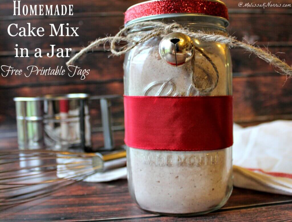 A jar of homemade cake mix tied with red ribbon and a bell.