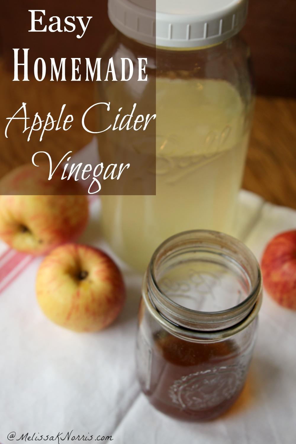 """Image of a quart Mason jar filled with apple juice in the background, and a pint Mason jar filled with apple cider vinegar in forefront. Two apples are sitting to the left, and one apple is sitting to the right. Text overlay says """"Easy Homemade Apple Cider Vinegar""""."""