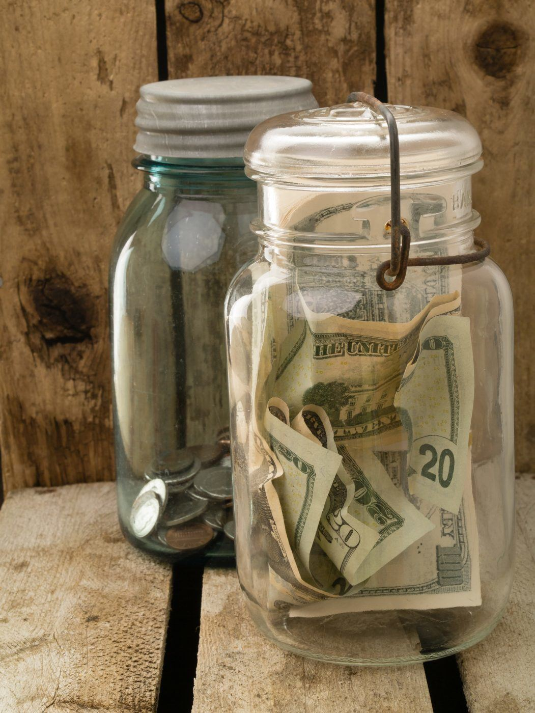 Two old Mason jars with paper money and coins.