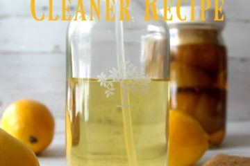 "Picture of a glass spray bottle filled with vinegar cleaner in the forefront, and a Mason jar filled with lemons and vinegar in the background. Fresh lemons are scattered in between. Text overlay says ""Natural Vinegar Cleaner Recipe""."