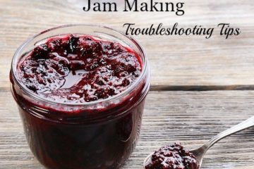 """Image of a jar of canned jam with a spoon filled with jam sitting on a wooden table. Text overlay says, """"10 Traditional Old-Fashioned Jam Making Troubleshooting Tips""""."""