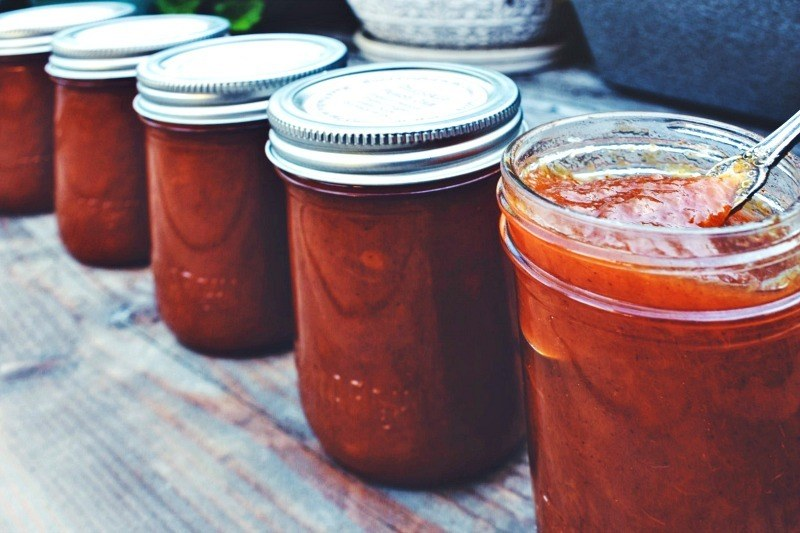 Image of three 8 ounce Mason Jars filled with spicy peach jam, stacked in a pyramid, and sitting on a whitewashed table. Placed in front of the jars is an additional opened 8 ounce Mason Jar filled with spicy peach jam with a spoon for serving. Text overlay say