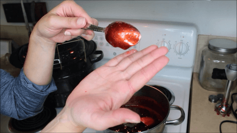 """A woman's hand holding up a spoon covered in jam as a """"Sheet test"""" to see if the jam has set."""