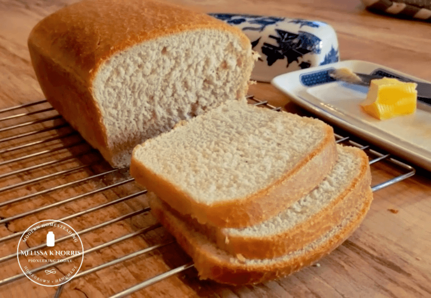 Sliced loaf of sourdough bread with butter in the background.