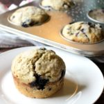 Blueberry zucchini muffin on a white plate with a muffin tin in the background.