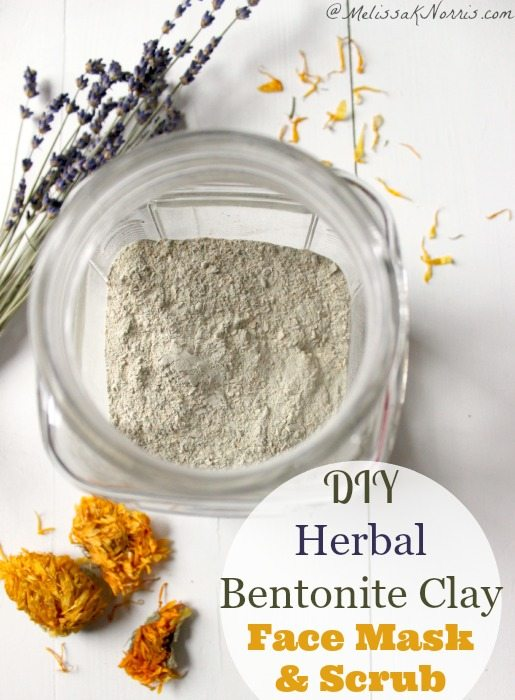 "Image is a bird's eye view of an open jar filled with Bentonite clay. Scattered around it are sprigs of dried lavender and dandelion heads. Text overlay says, ""DIY Herbal Bentonite Clay Face Mask and Scrub""."