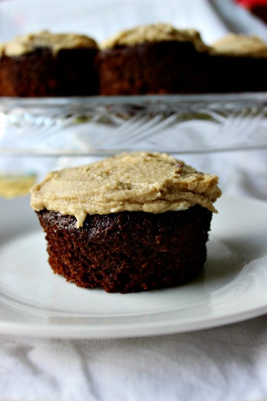 """Close up image of a frosted chocolate cupcake on a white plate with a cake tray full of cupcakes in the background. Text overlay says, """"Chocolate Mayo Cupcakes with Caramel Frosting""""."""