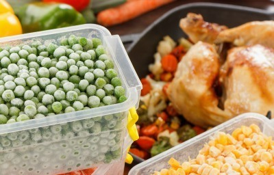 Frozen containers of peas and corn being added to a chicken dish.