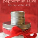 """Pinterest pin with an image of various sized round tins stacked on top of each other, and tied with a bow. Text overlay reads """"Homemade Peppermint Salve (for dry winter skin)""""."""