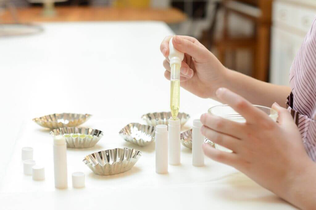 A photo of someone making homemade lip balm, using a dropper adding the liquid into tubes.