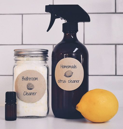 """Image of an amber spray bottle and a quart Mason Jar filled with homemade cleaners against a white tile backdrop. A bottle of essential oil and a fresh lemon sit to the side. Text overlay says, """"5 Homemade Natural Cleaner Recipes""""."""