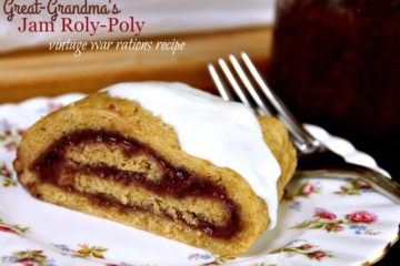 "Image of a slice of jam roly poly served on a decorative plate. A jar of raspberry jam is sitting in the background. Text overlay says, ""Great-Grandma's Jam Roly Poly - Vintage War Rations Recipe""."