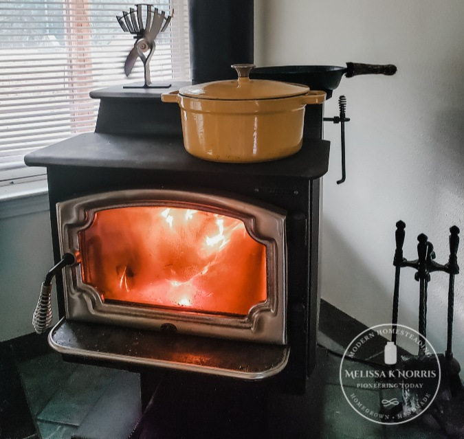 Picture of a wood stove with a pot on top.