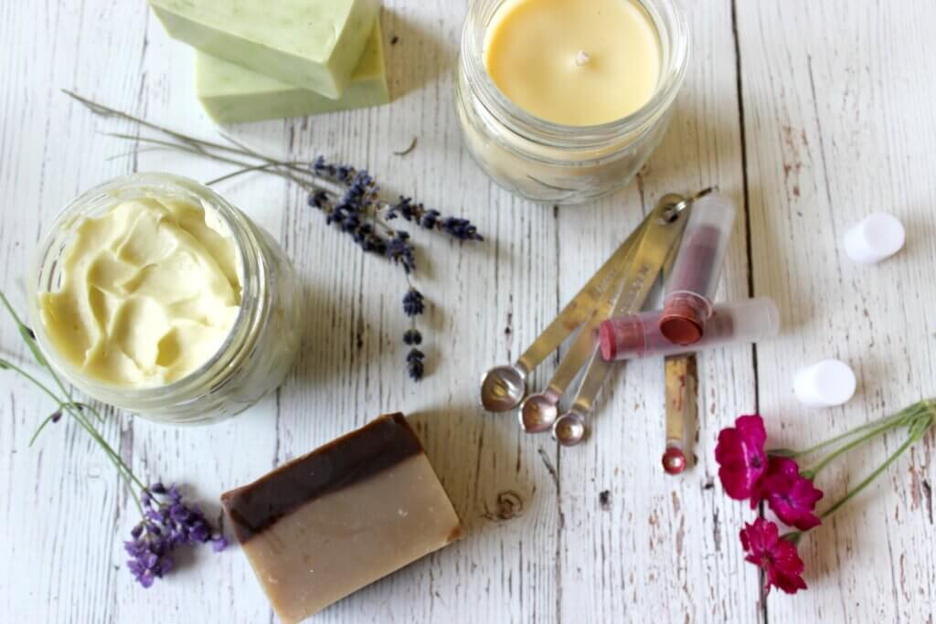 Homemade personal care items like lip balm, body butter and homemade soap sitting on a counter.