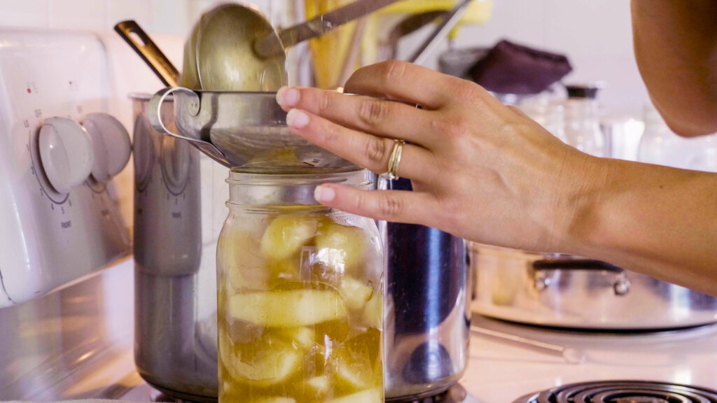 A woman ladling apple pie filling into a mason jar.