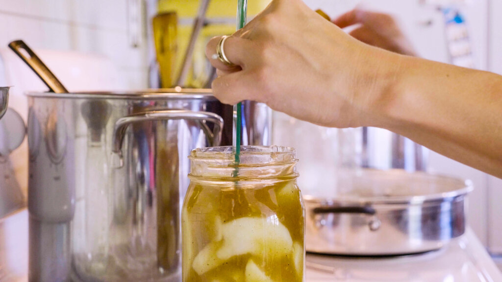 A woman's hand measuring the head space in a mason jar filled with apple pie filling.