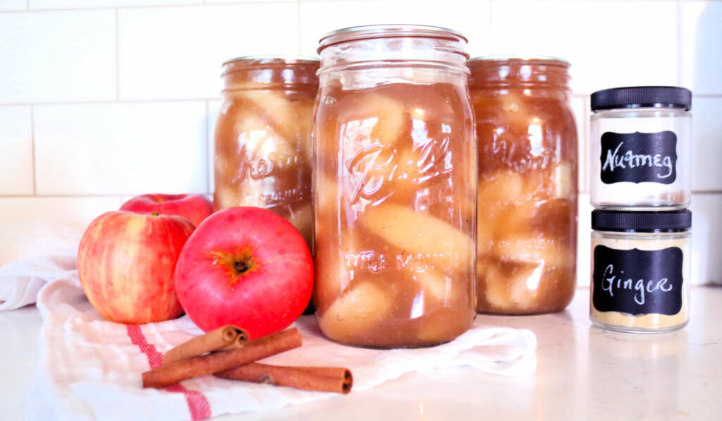 Jars of home canned apple pie filling sitting on a counter next to apples, cinnamon sticks and other spices.