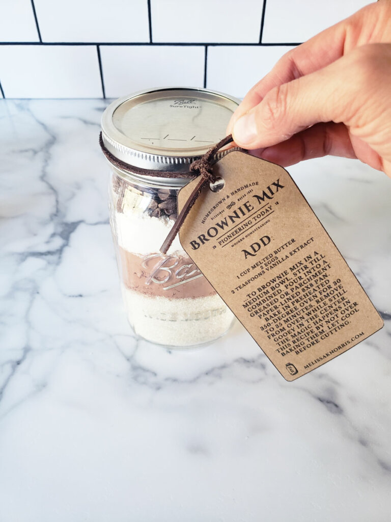 A tag being added to a mason jar filled with brownie mix ingredients.