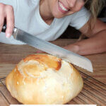 Pinterest pin for artisan bread with an image of a woman slicing into a fresh baked loaf.
